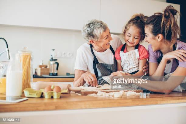 lovely little girl cooking with mom and granny - multigenerational family stock photos and pictures
