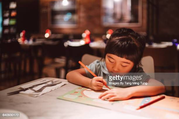 Lovely little girl drawing on a piece of paper in a restaurant