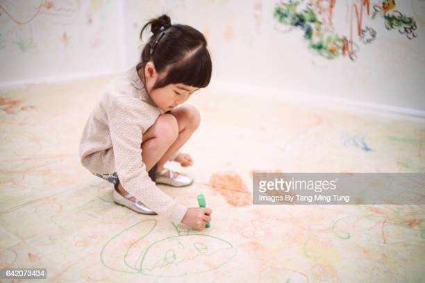Lovely little girl drawing with crayons on the floor.