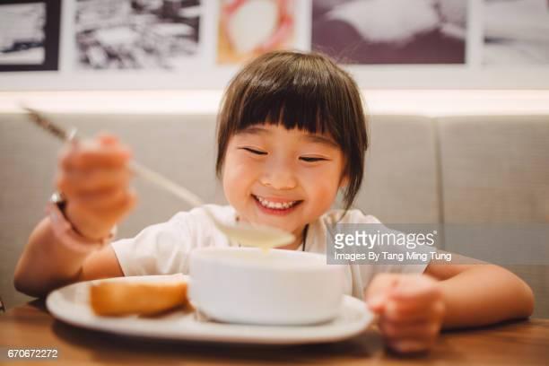 lovely little girl enjoying a bowl of soup in a restaurant joyfully