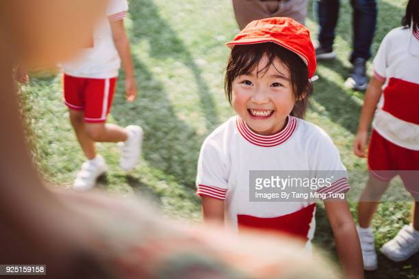 Lovely little girl enjoying quality times with parents at school's sports day joyfully.
