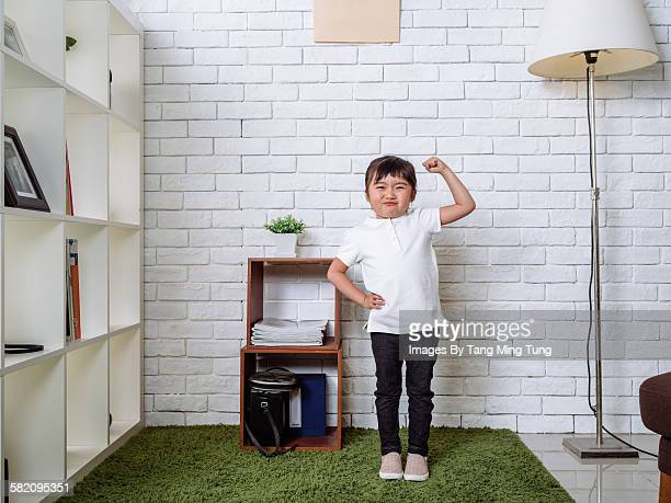 lovely little girl flexing muscles in living room - flexing muscles stock pictures, royalty-free photos & images