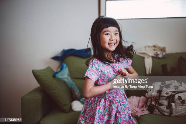 lovely little girl getting dressed joyfully by herself at home in the morning - one girl only stock pictures, royalty-free photos & images
