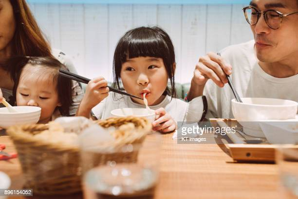 Lovely little girl having a bowl of noodles with her family joyfully.