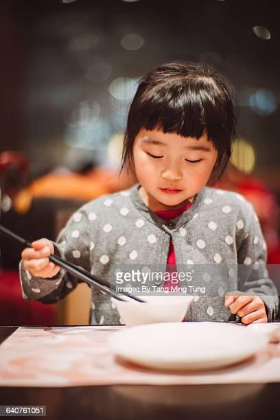 Lovely little girl having meal with chopsticks