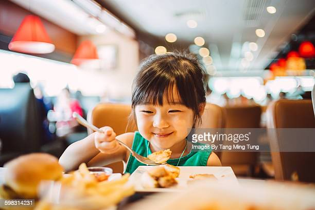 Lovely little girl having meals joyfully