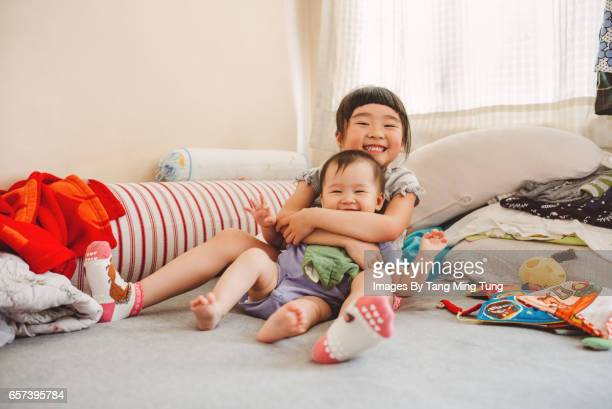 Lovely little girl hugging and playing with her baby sister on the bed while smiling at the camera joyfully