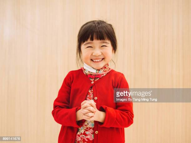 lovely little girl in chinese custom posing kung hei fat choy while smiling at camera joyfully. - chinese new year stock pictures, royalty-free photos & images