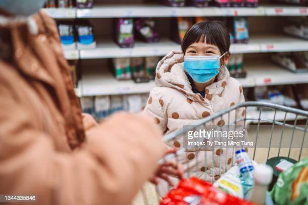 lovely little girl in protective face mask having fun while out buying groceries with family in supermarket. - flatten the curve stock pictures, royalty-free photos & images