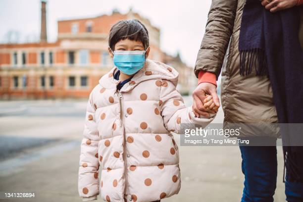 lovely little girl in protective face mask smiling joyfully at the camera while strolling along the street with her mom in town - flatten the curve stock pictures, royalty-free photos & images