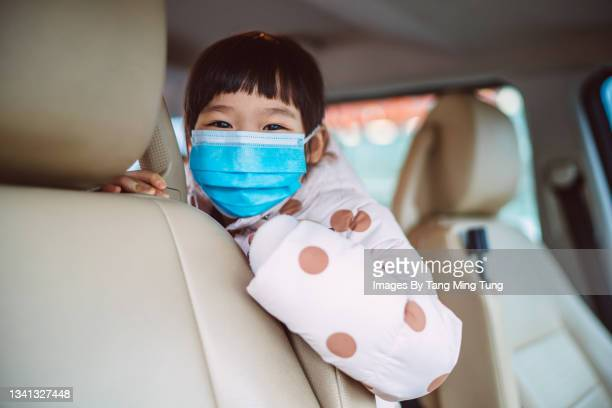 lovely little girl in protective face mask smiling joyfully at the camera in a car - flatten the curve stock pictures, royalty-free photos & images