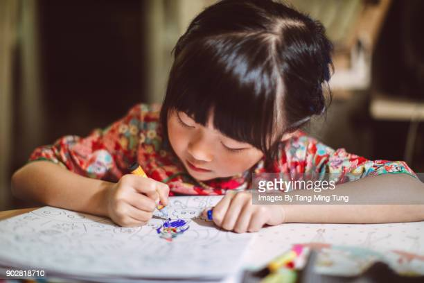 lovely little girl in traditional chinese costumes colouring in a colouring book. - colouring book stock pictures, royalty-free photos & images