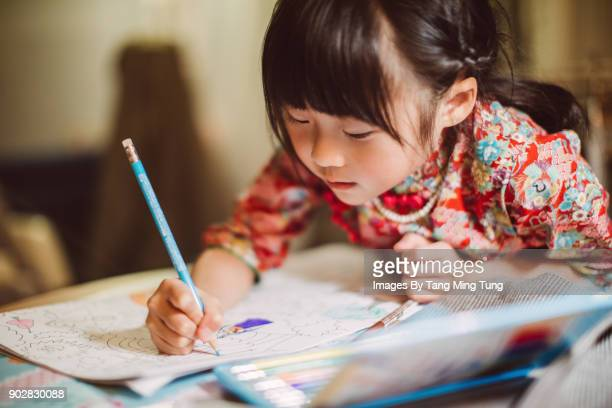 lovely little girl in traditional chinese costumes colouring in a colouring book happily. - arti e mestieri foto e immagini stock
