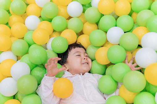 Lovely little girl playing joyfully in ball pit - gettyimageskorea