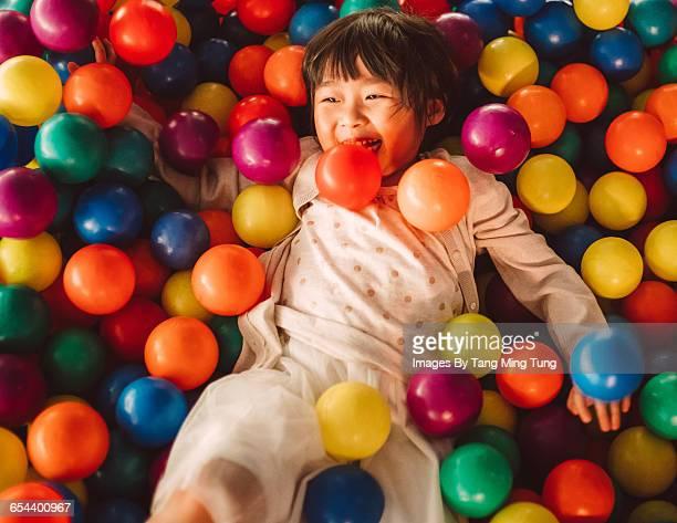 Lovely little girl playing joyfully in ball pit