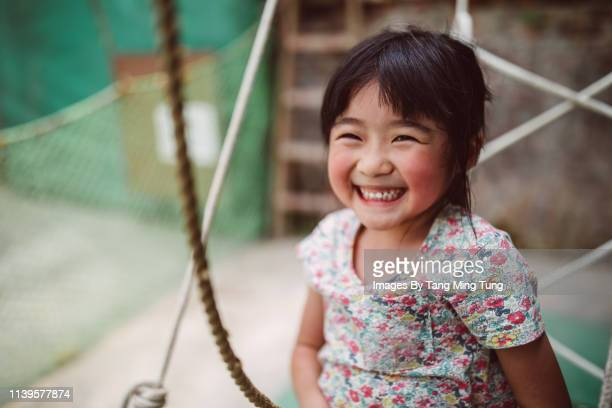 Lovely little girl playing joyfully on the tire swing in playground