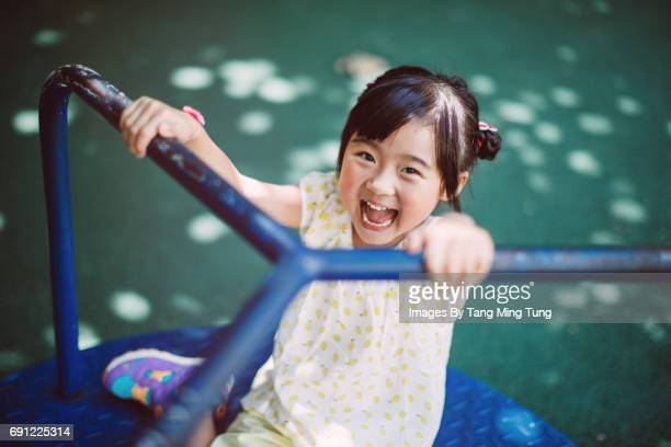 Lovely little girl playing on the merry go round in the playground joyfully