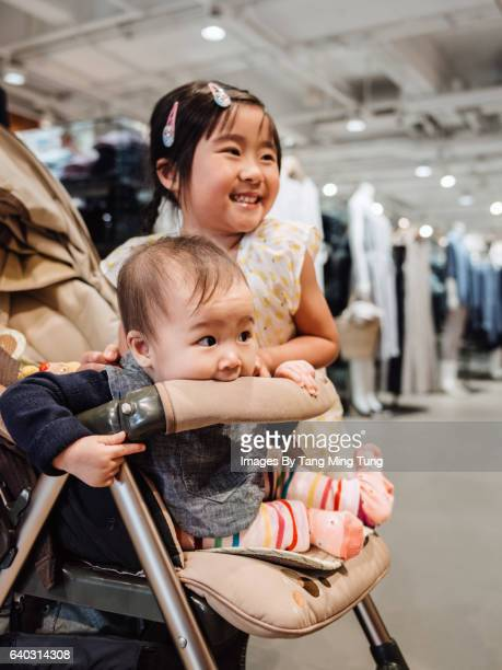 Lovely little girl playing with her baby sister in a fashion boutique.