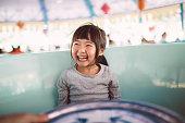 lovely little girl riding amusement park