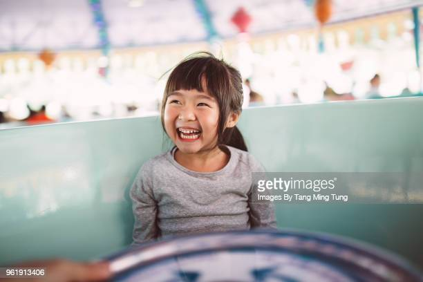 lovely little girl riding on the amusement park ride joyfully. - ming stock photos and pictures