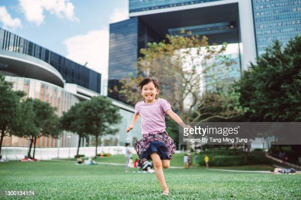 lovely little girl running in park joyfully - asia stock pictures, royalty-free photos & images