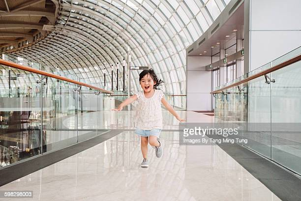 Lovely little girl running joyfully in mall