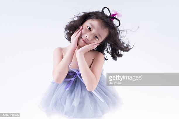 Lovely little girl sitting joyfully in a studio in Xiangyang Hubei province China in 2015 Wang Yuwen