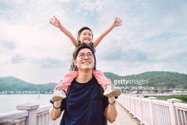 lovely little girl sitting on dad's shoulders joyfully - genderblend stock pictures, royalty-free photos & images