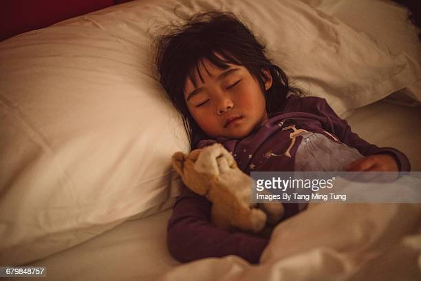 Lovely little girl sleeping soundly on the bed