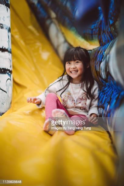 Lovely little girl sliding on a inflatable slide joyfully.