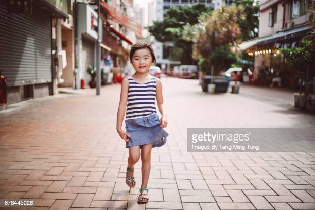 lovely little girl smiling and walking towards the camera joyfully - little girls up skirt fotografías e imágenes de stock