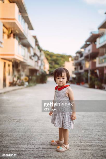 Lovely little girl smiling at camera in a modern village.