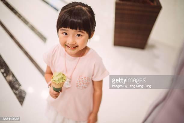 Lovely little girl smiling at the camera joyfully while having an ice-cream