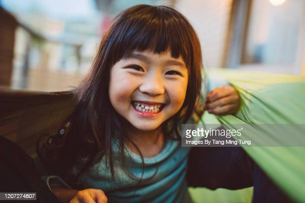 lovely little girl smiling at the camera while playing joyfully in hammock - one girl only stock pictures, royalty-free photos & images