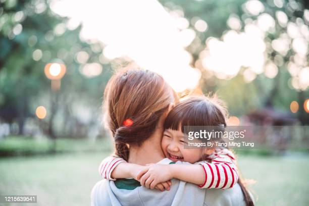 lovely little girl smiling joyfully while her mom carrying her in park - east asian ethnicity stock pictures, royalty-free photos & images