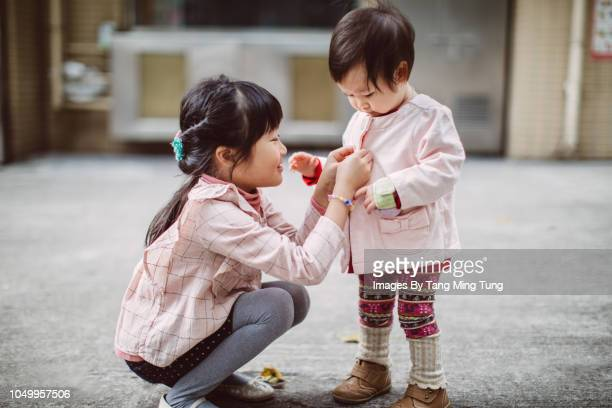 Lovely little girl squat down and helping her toddler sister to put on clothes on the street in winter.