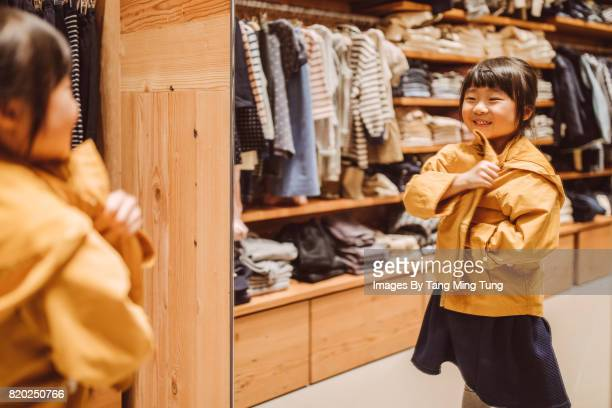 Lovely little girl trying out a jacket in front of a mirror joyfully in a department store
