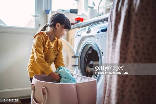 lovely little girl unloading the washing machine while helping her mom with laundry at home - laundry stock pictures, royalty-free photos & images