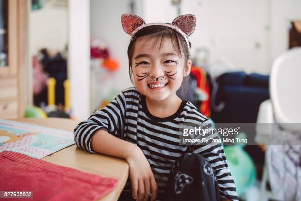 Lovely little girl wearing a cat face painting smiling at camera joyfully at home.