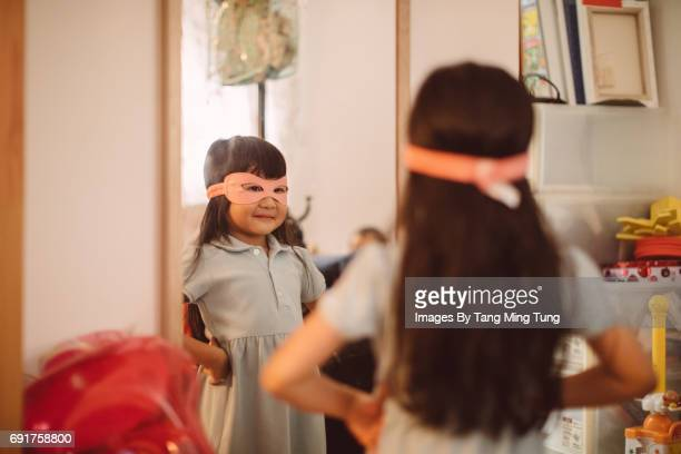 Lovely little girl wearing a superwomen mask looking into the mirror with pride