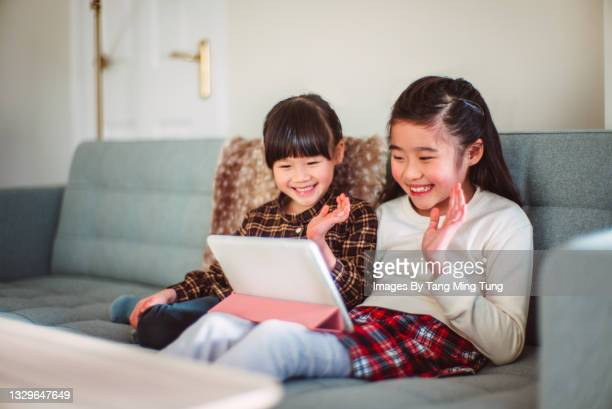 lovely little sister having video call joyfully on digital tablet at home - digital native stock pictures, royalty-free photos & images