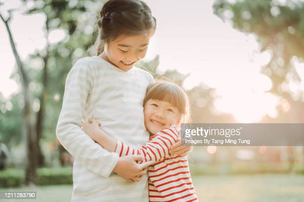 lovely little sisters hugging & smiling joyfully in park - east asian ethnicity stock pictures, royalty-free photos & images