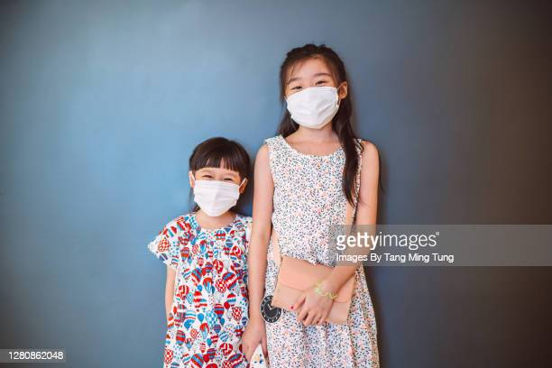lovely little sisters in protective face masks looking & smiling at the camera joyfully - side by side stock pictures, royalty-free photos & images