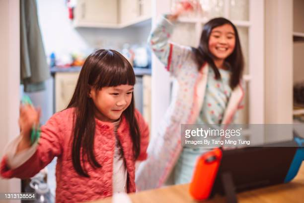 lovely little sisters in their pyjamas playing video game at home joyfully - hong kong stock pictures, royalty-free photos & images
