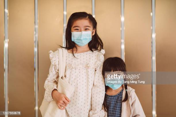 lovely little sisters with medical face masks looking & smiling joyfully at camera - side by side stock pictures, royalty-free photos & images