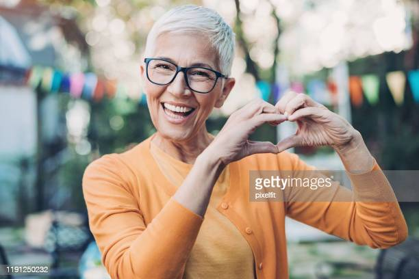 lovely mature woman making heart shape with hands - human body part stock pictures, royalty-free photos & images