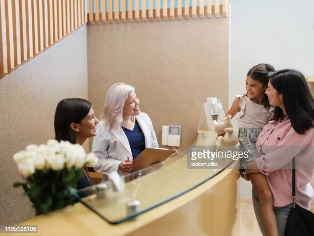 lovely mother carrying little girl at dental clinic's reception desk - dentist's office stock pictures, royalty-free photos & images