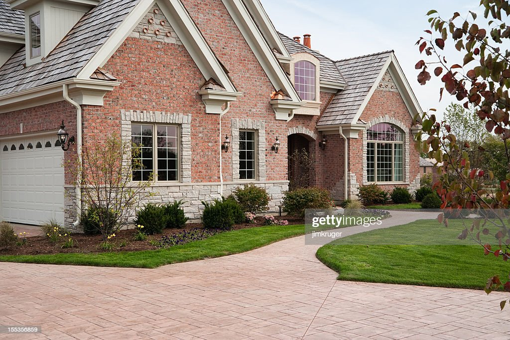 Lovely red brick upscale home with concrete driveway. : Stock Photo