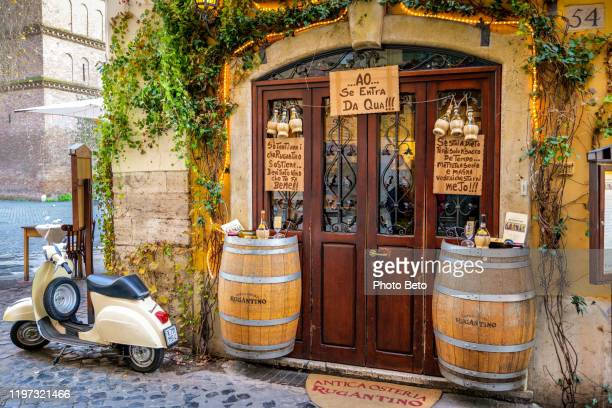 a lovely roman restaurant in the ancient trastevere district with a vintage vespa - vespa brand name stock pictures, royalty-free photos & images