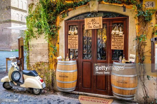 ein typisch römisches restaurant in trastevere mit einer vespa im freien - vespa stock-fotos und bilder